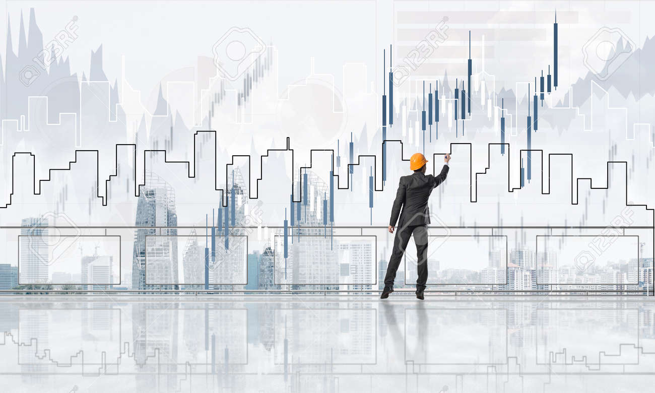 Young engineer in suit at balcony against morning cityscape background - 120193665