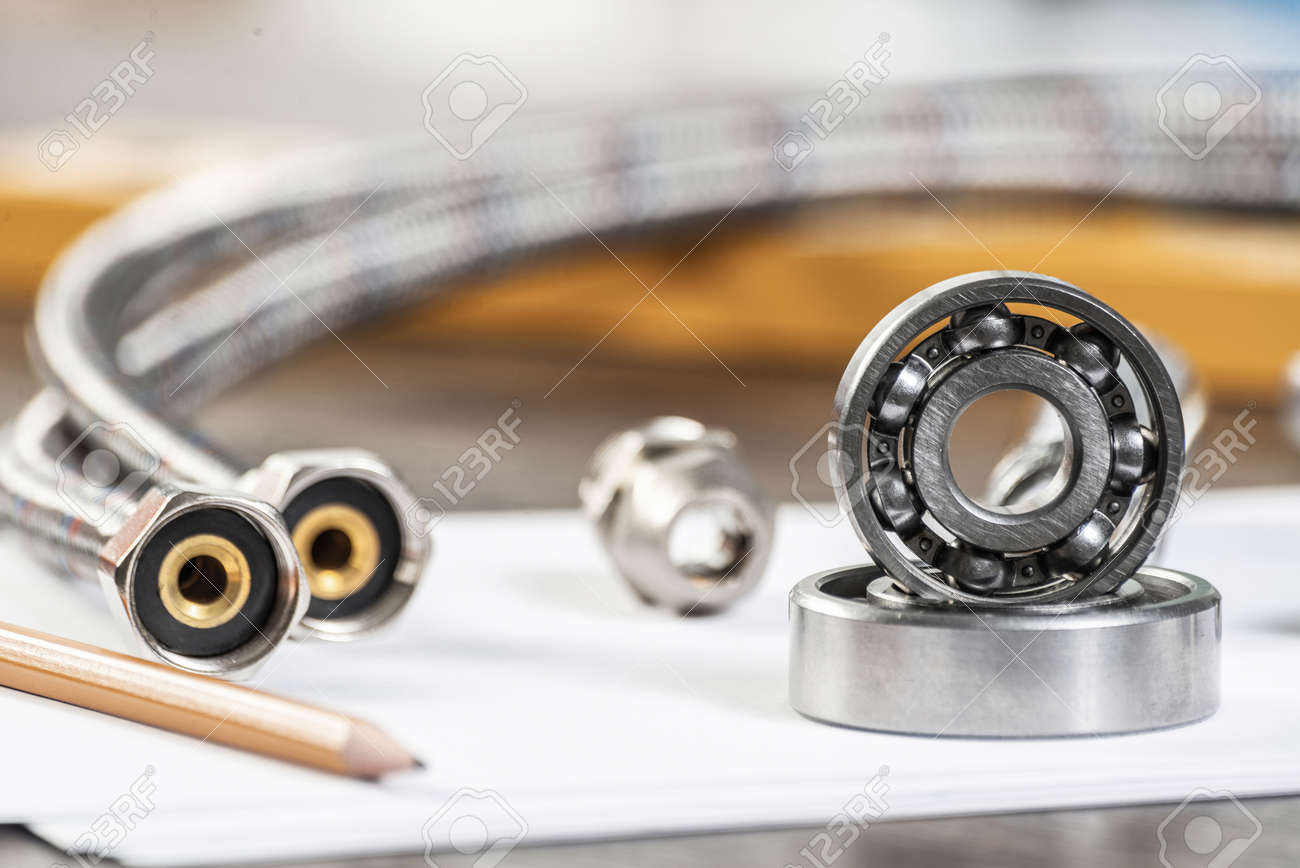 Plumbing pipeline and ball bearings laying on table. Water fittings and connections with segments of braided hose. Steel details for engine mechanisms. House infrastructure designing and installation - 127736617