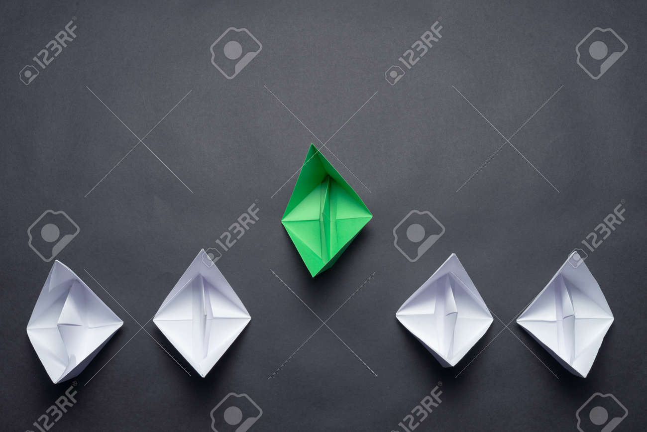 Flat lay green origami origami leader boat ahead others boats. Row of paper ships on black background. Individual motivation and direction. Creative innovation and leadership. Social marketing layout. - 128187726