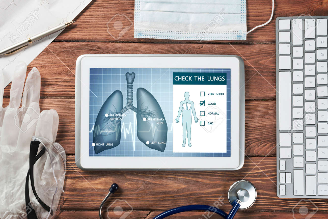 White tablet pc and doctor tools on wooden table - 134034424