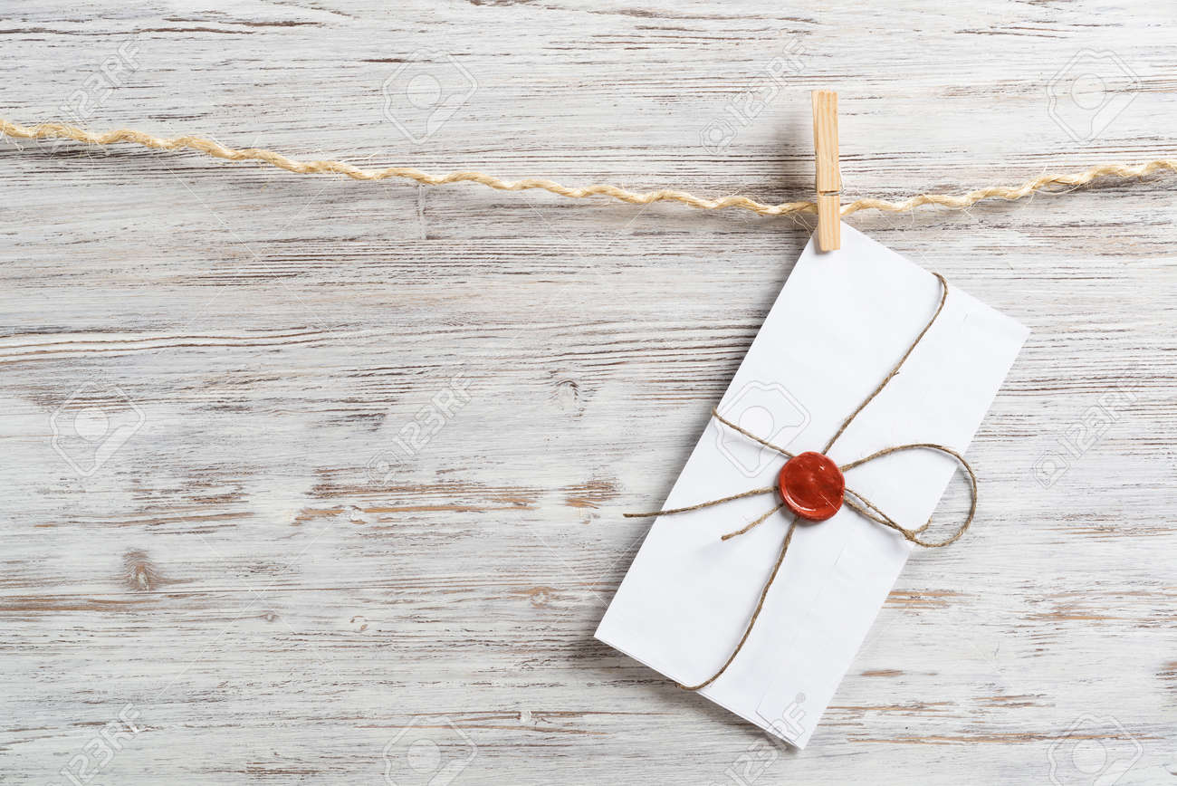 White envelope hanging on rope on wooden background. Twine rope with wooden clothespins. Letter envelope with wax seal stamp. Retro communication and correspondence. Delivery service layout - 136432408