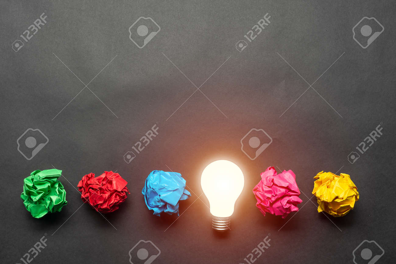 Lightbulb and crumpled colorful paper balls on black background. Successful solution of problem. Idea generation and brainstorming. Genius idea among failing ideas metaphor. Business motivation - 139590861