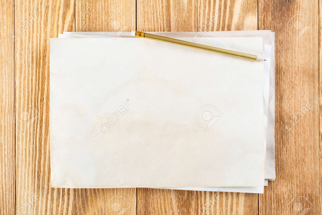 Sheet of paper lying on wooden table. Blank white a4 format paper with pencil. Textured natural wooden background. Vintage copy space for design. Business planning and idea generation. - 145520502