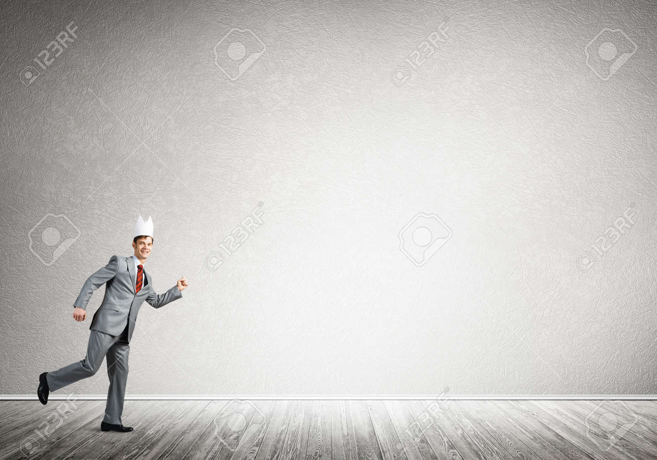 Young handsome businessman wearing white paper crown running in a hurry - 146958420