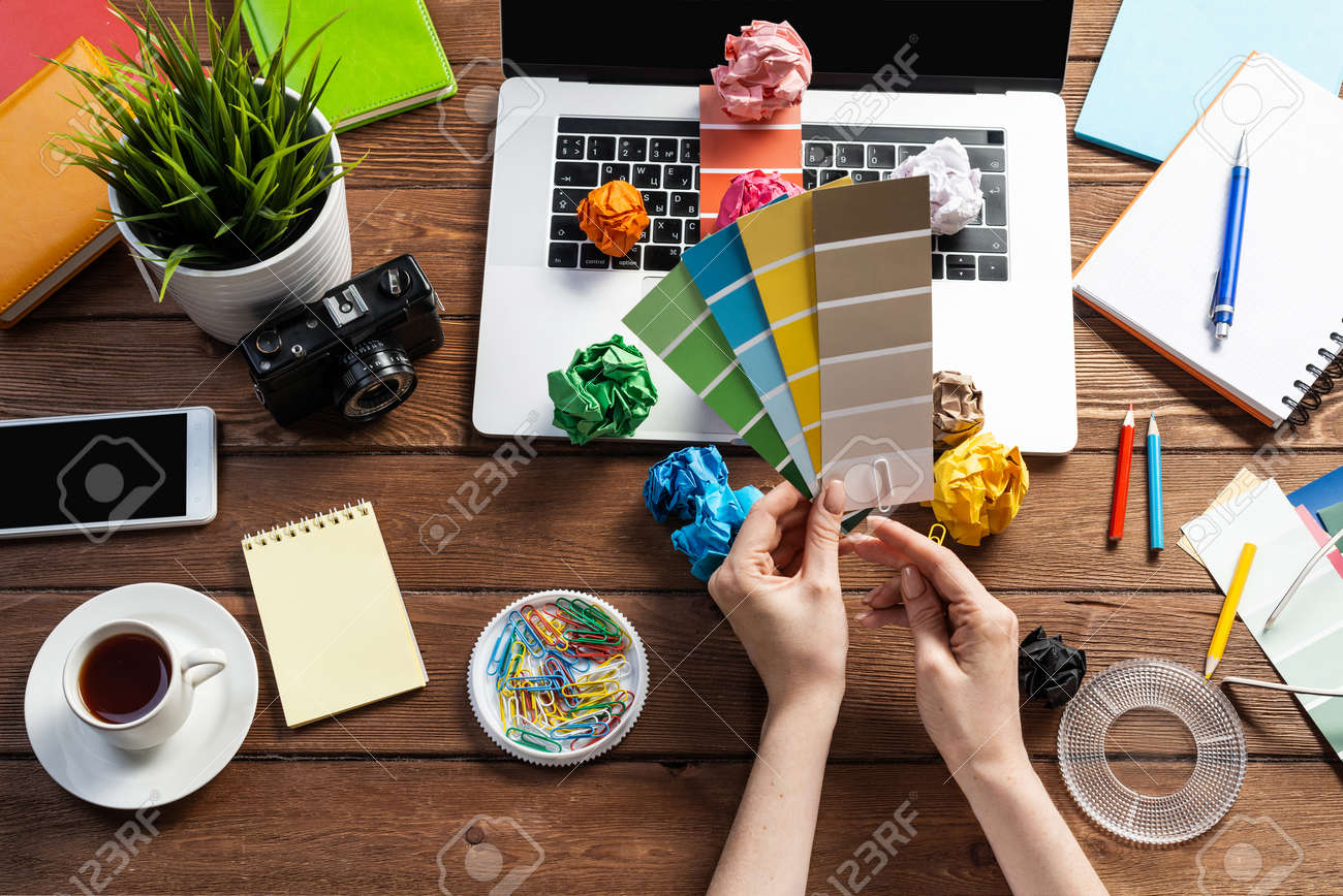 Interior designer choosing colors from swatches at wooden desk. Office workplace with laptop and stationery. Selection of color palette for design. Professional house renovation and interior redesign. - 147371595