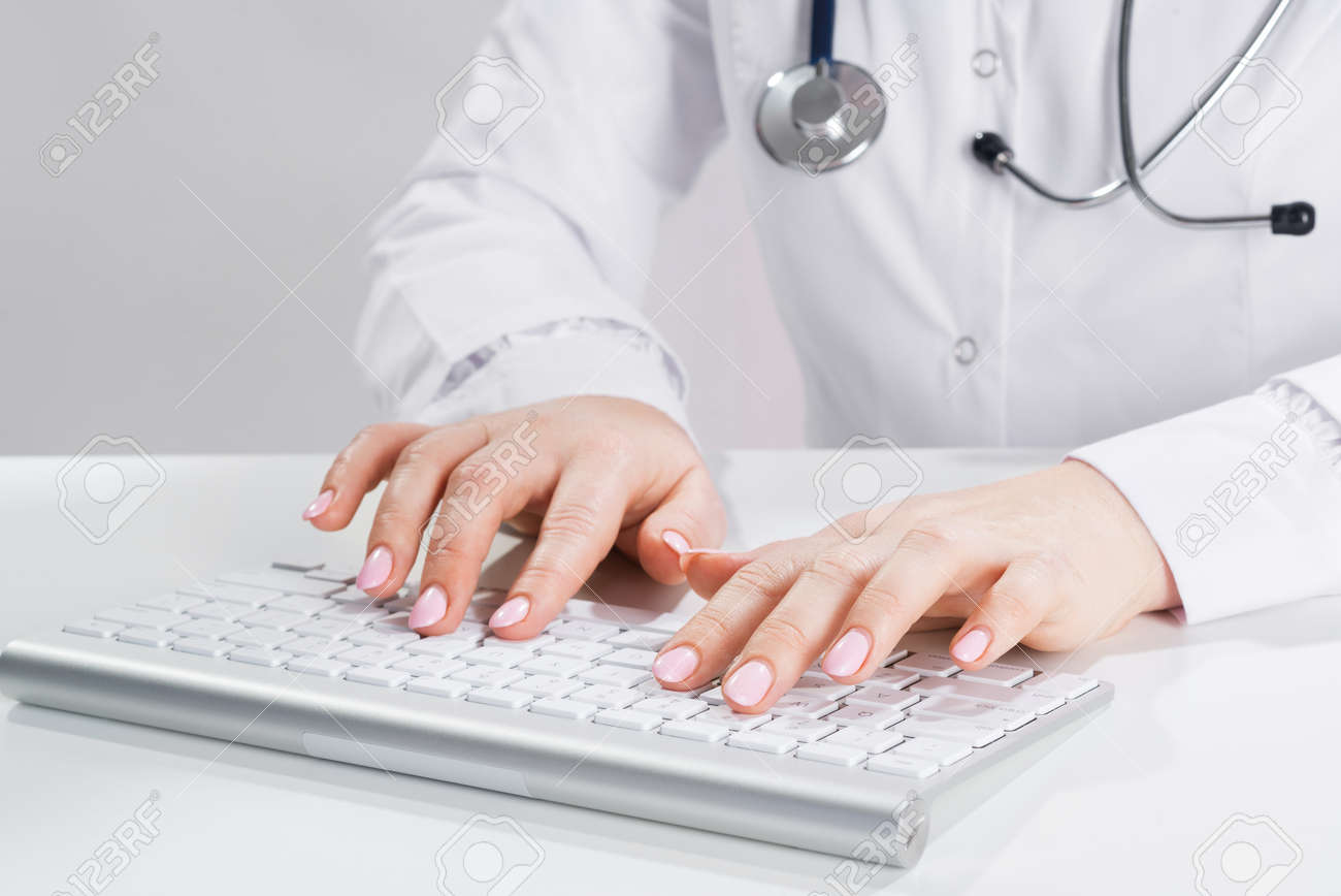 Close up doctor typing on computer keyboard. Female physician in white coat with stethoscope sitting at desk. Professional medical diagnosis and treatment in clinic. Healthcare and medicine. - 148682399