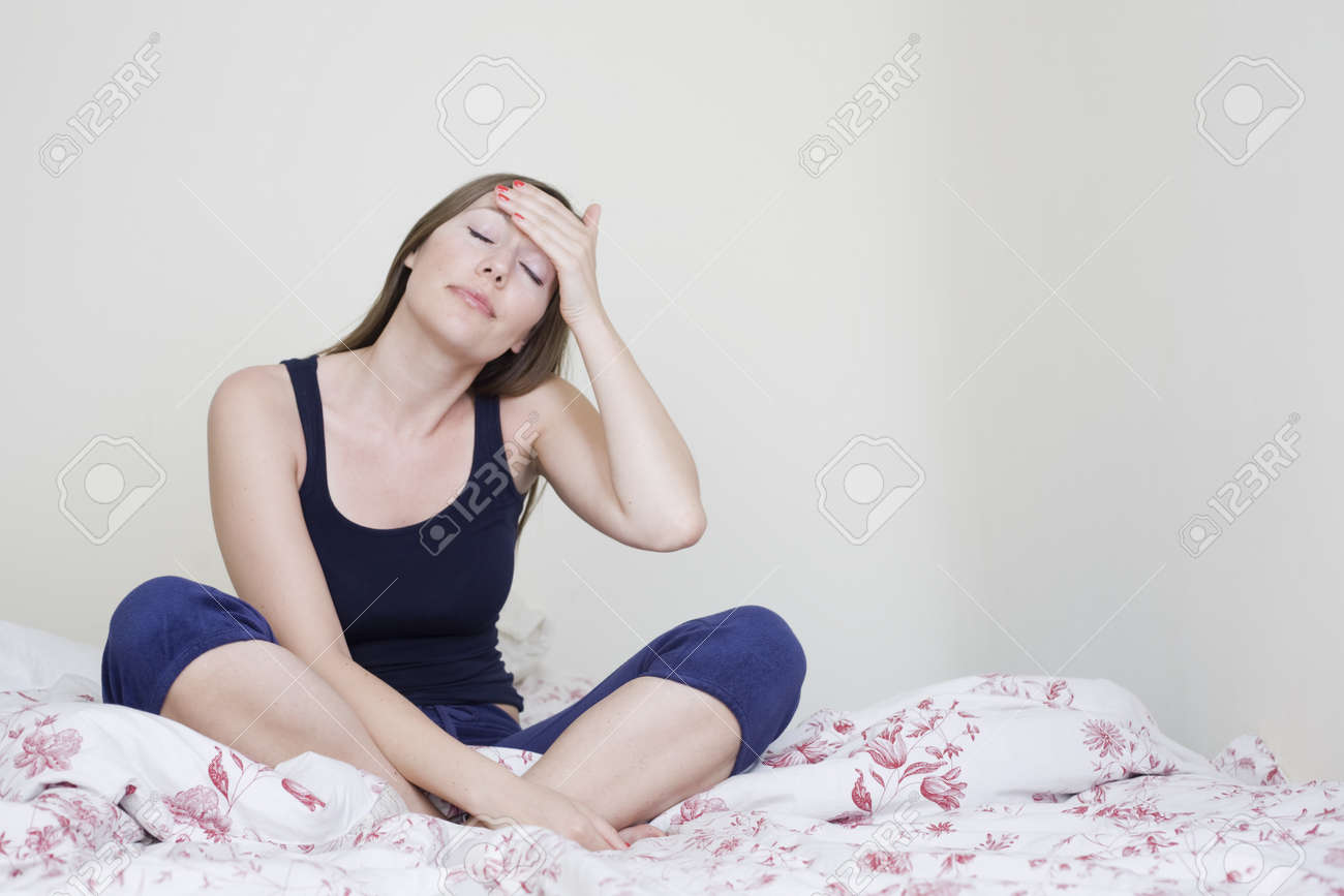 Young caucasian woman having headache sitting in bad Stock Photo - 12525614