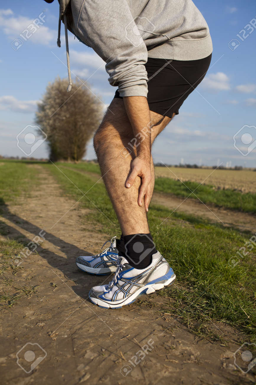 Man touching his thigh during running because of pain Stock Photo - 15277387
