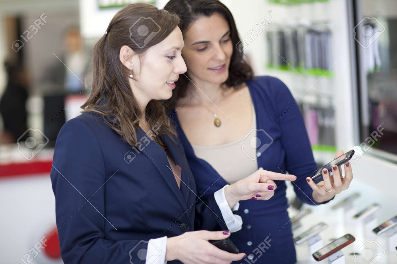 Woman choosing a phone in a cell phone shop Stock Photo - 17413222
