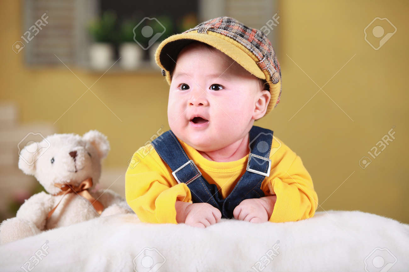 Happy Cute 3 Month Old Chinese Baby Boy Playing On Bed With Colorful