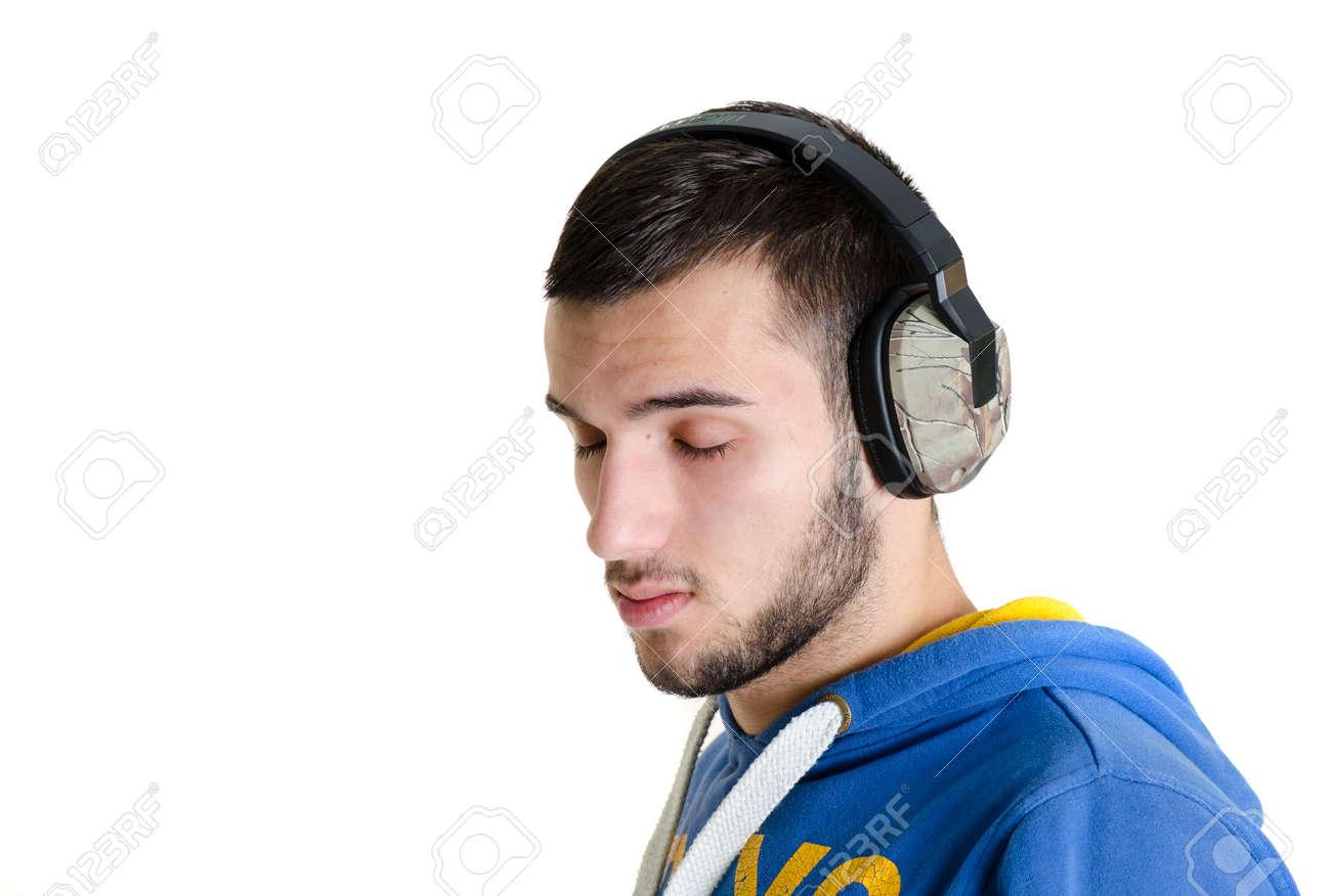 42557fa6ab85 Standard-Bild - Teenager Mann entspannt Musik hört auf Ohr-Kopfhörern mit geschlossenen  Augen auf weißen Hintergrund