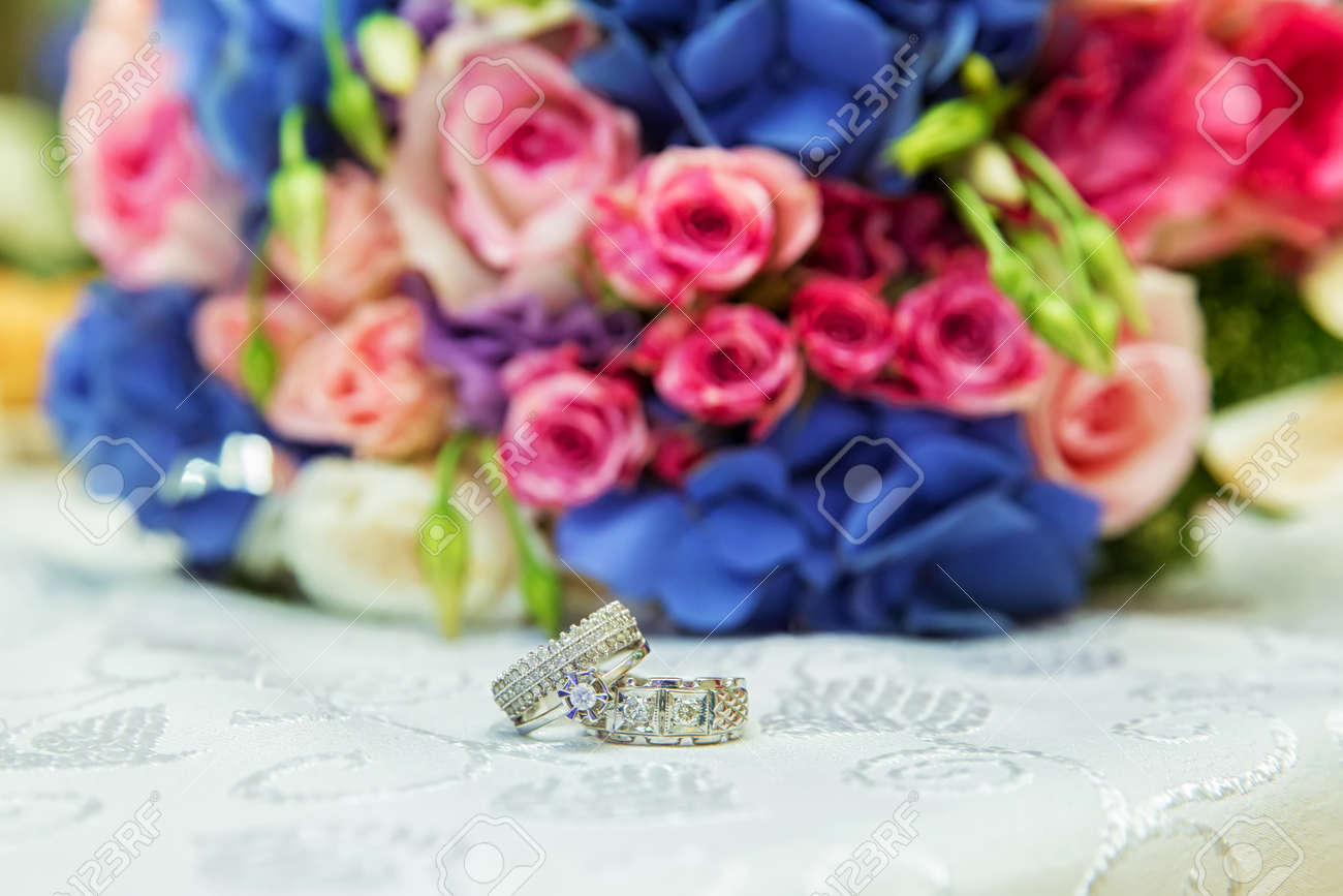 Mens and bridal rings are on the background of a multi colored mens and bridal rings are on the background of a multi colored wedding bouquet stock izmirmasajfo