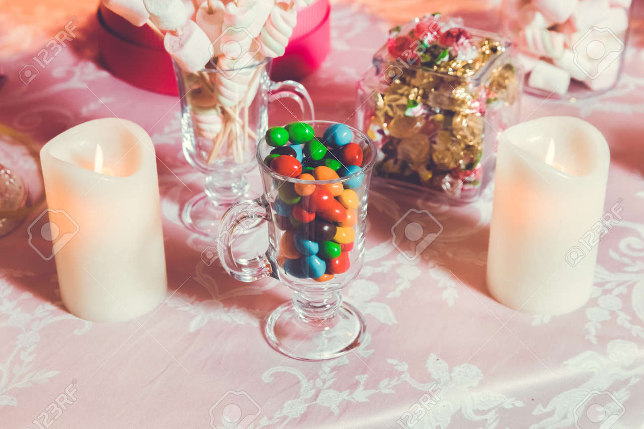 Multi colored sweets . Colored candy in a glass . Round chocolate is very colorful - 120161232