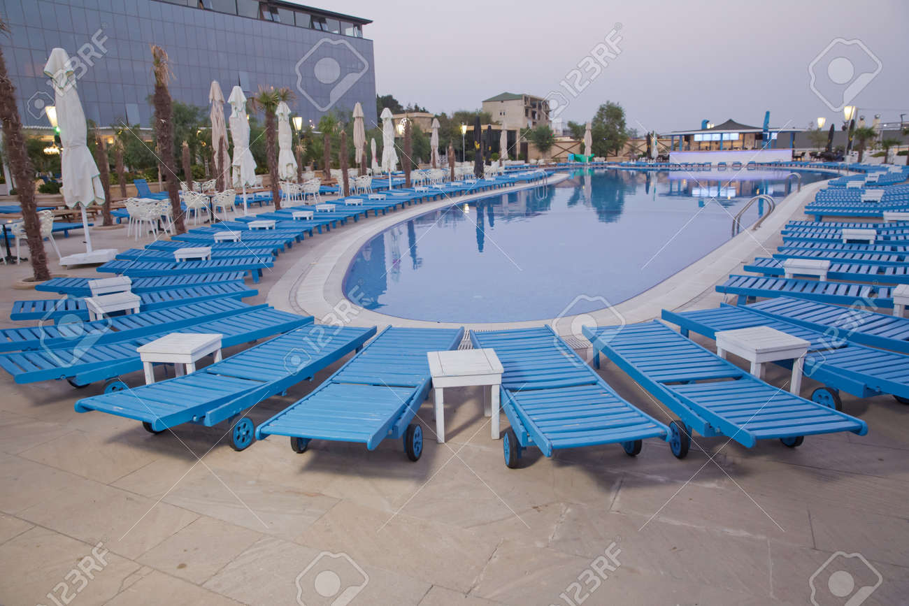 Empty sunbeds by the beautiful resort pool . Lounge sunbeds near..
