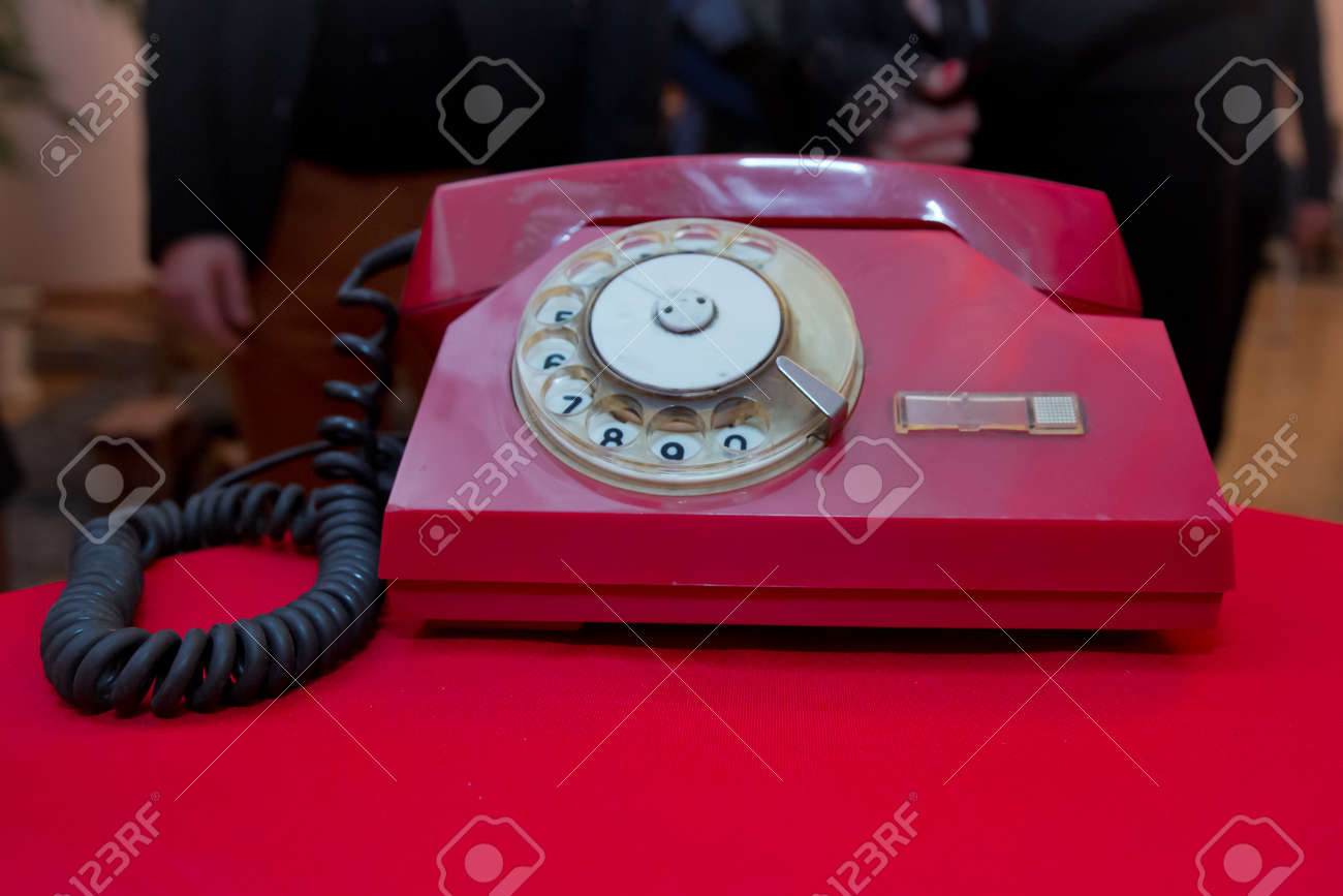Red antique vintage analog telephone dialing or scrolling phone on red table. Contact us concept .Still life with retro red phone on wooden red table over grunge background - 129928000