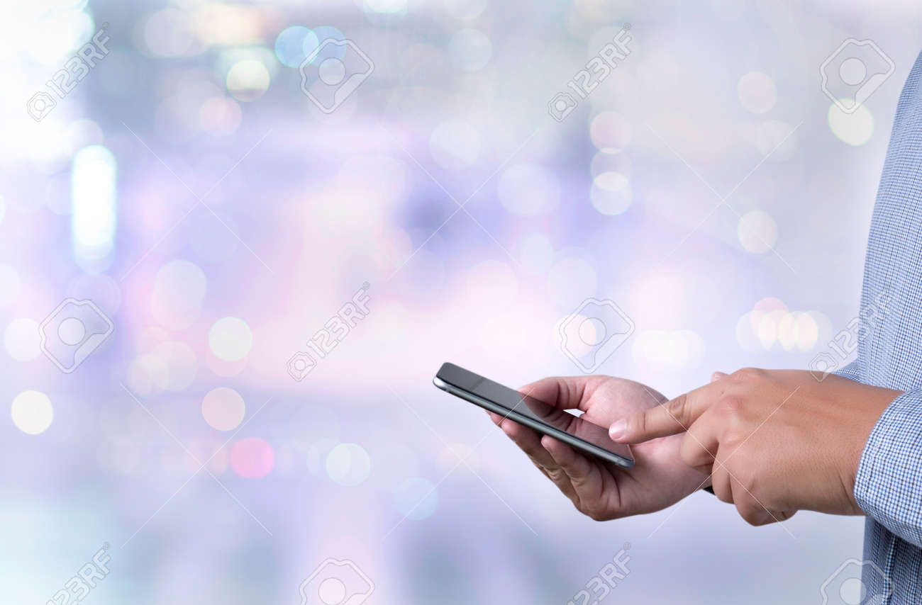 person holding a smartphone on blurred cityscape background - 52976370