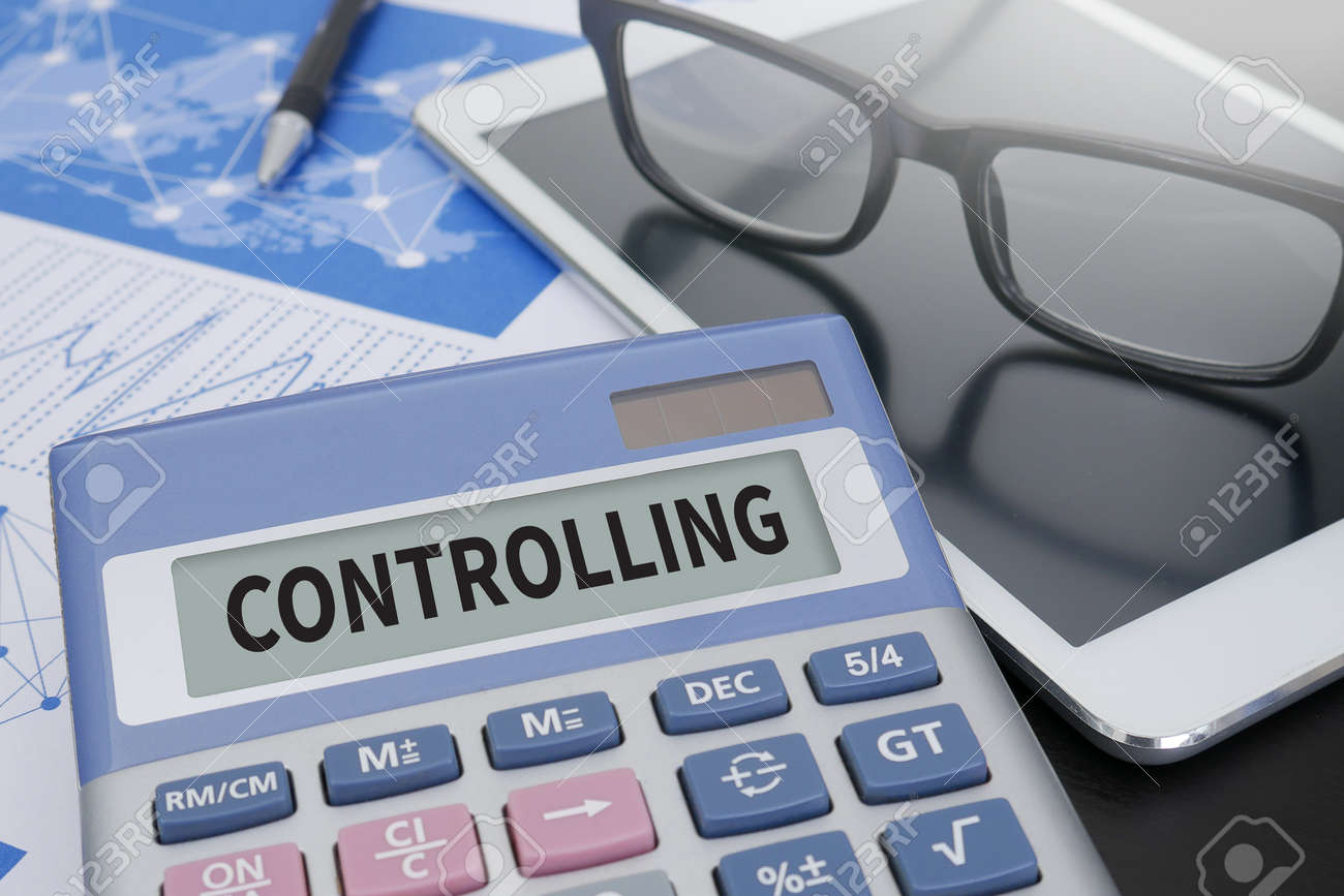 controlling calculator on table with office supplies stock photo