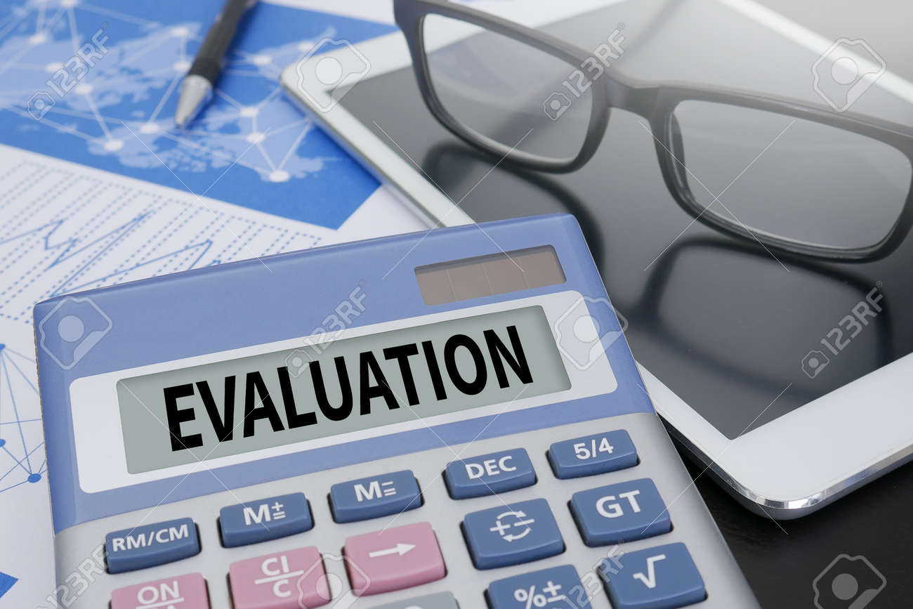Evaluation Calculator On Table With Office Supplies Stock Photo