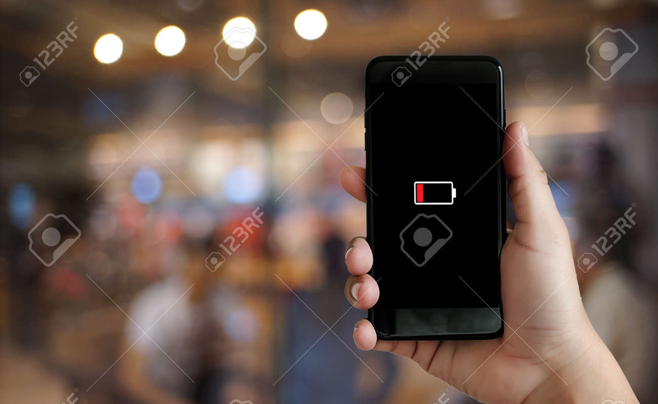 Close up man hands using smart phone battery low charged battery screen - 99702448