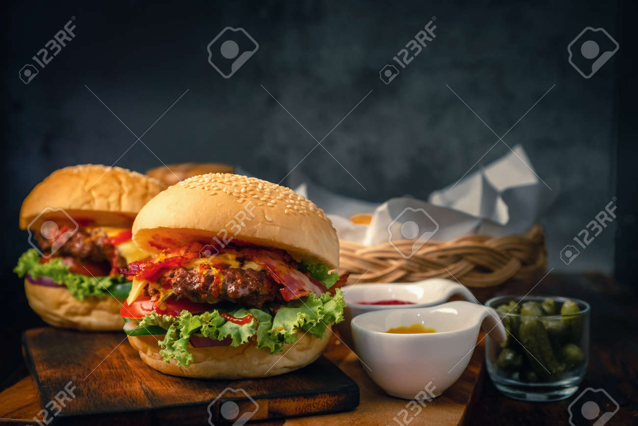 Delicious 2 home made hamburger with beef, ketchup, mustard and fresh vegetables served on wooden board. Free space for text - 125609233
