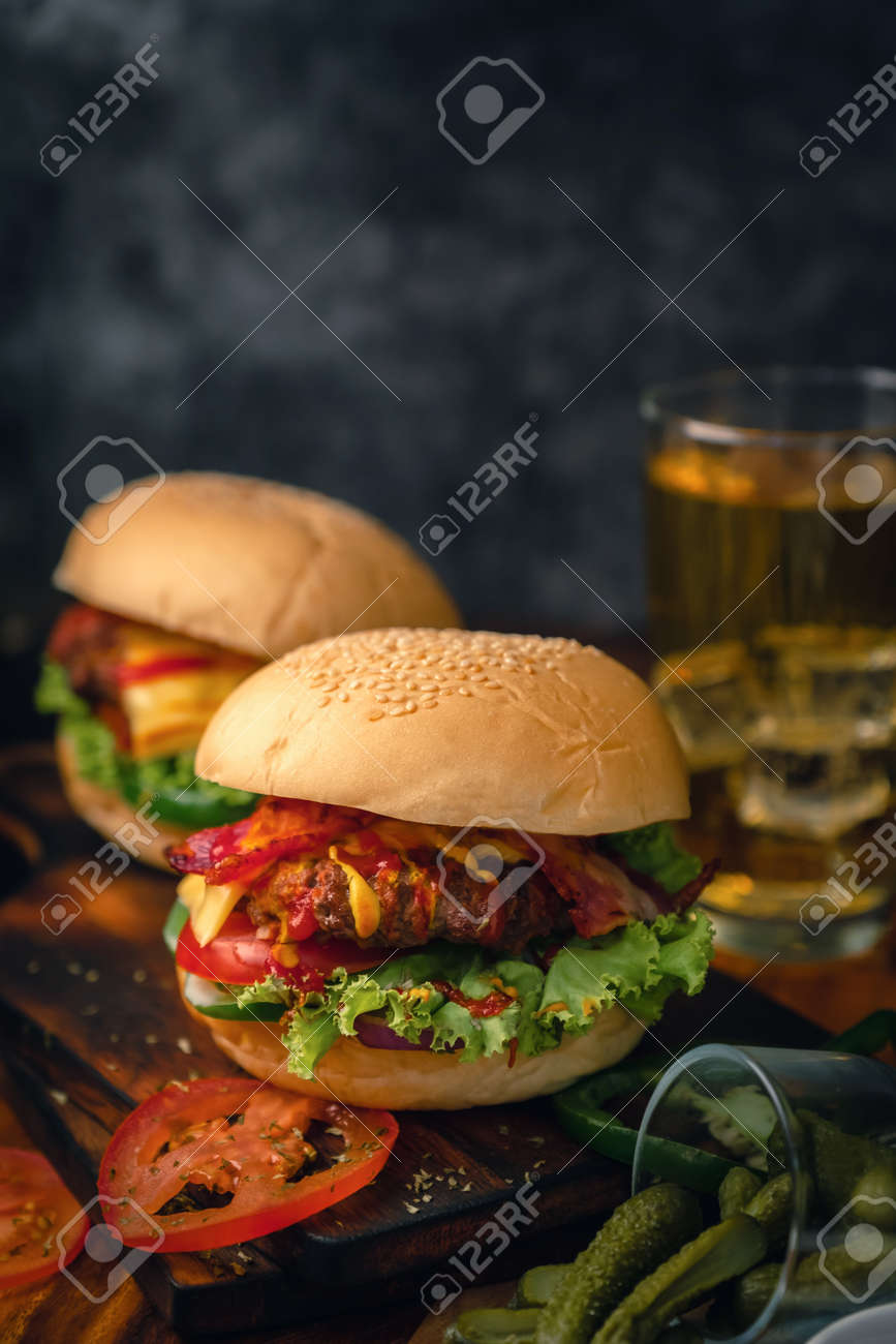 Delicious home made hamburger with beef, ketchup, mustard and fresh vegetables served on wooden board. Free space for text - 125609254