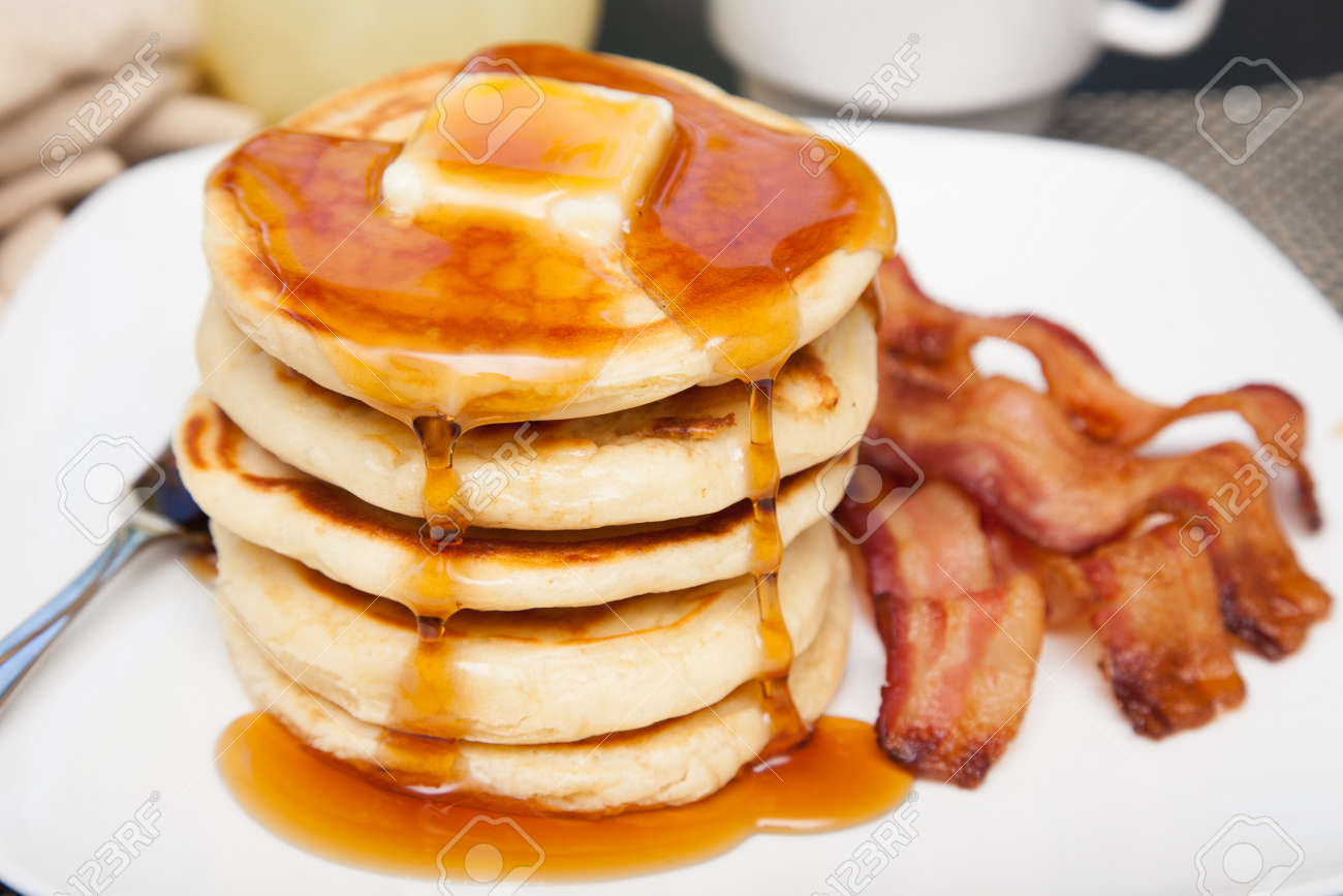 A tall stack of pancakes with butter and dripping syrup and three strips of bacon - 47230315