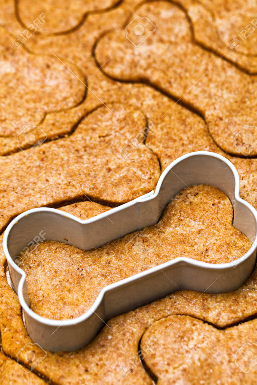 Fresh dog biscuit dough with bone-shaped cookie cutter - 59099397