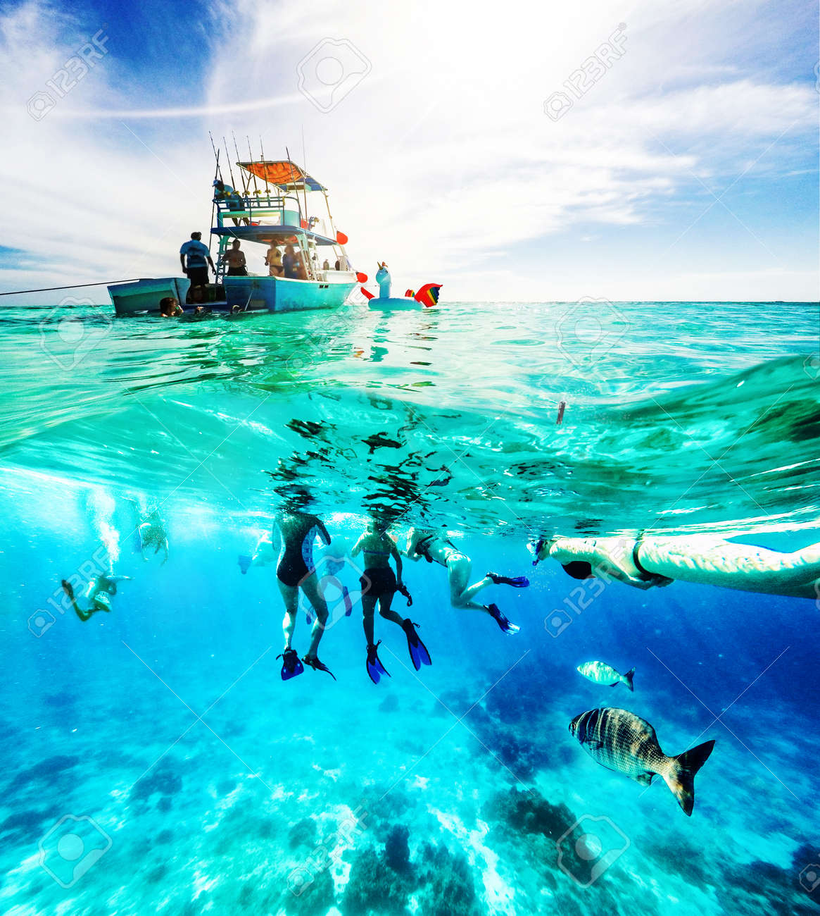 Group of friends on a Carribean Sea adventure with party boat, snorkeling and scuba diving - 100972811