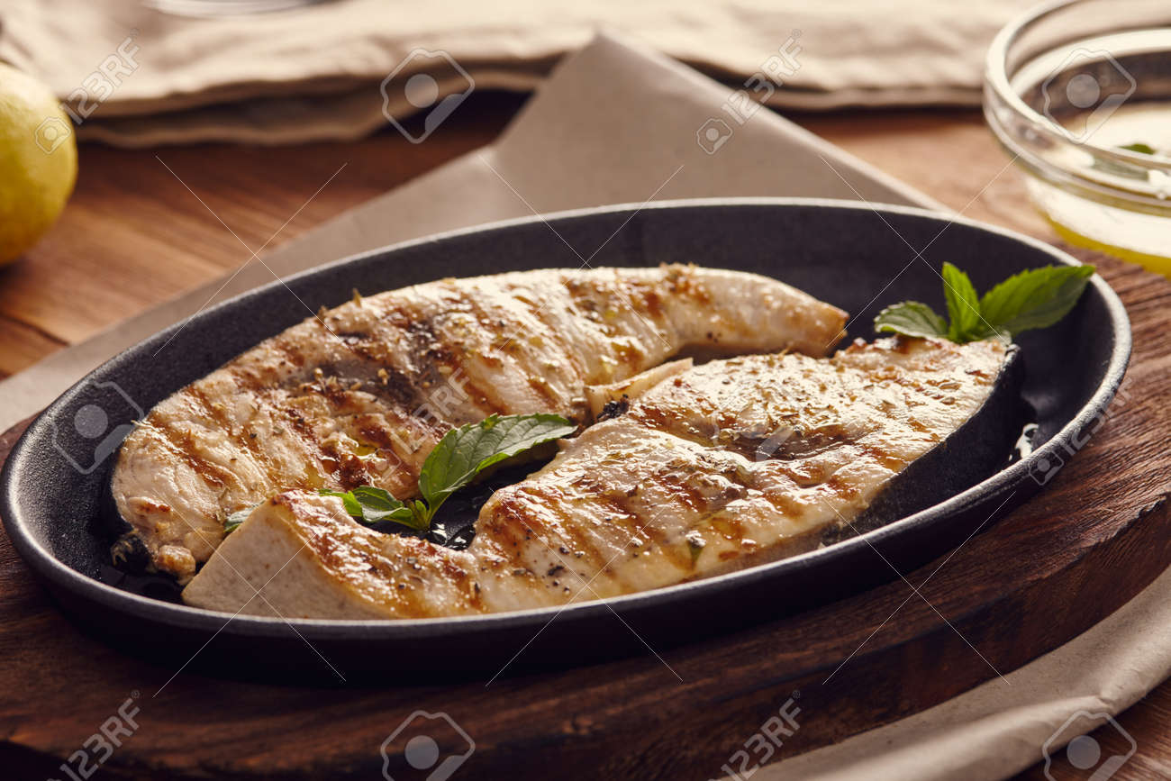 grilled swordfish slices in a cast iron pan on a wooden table,