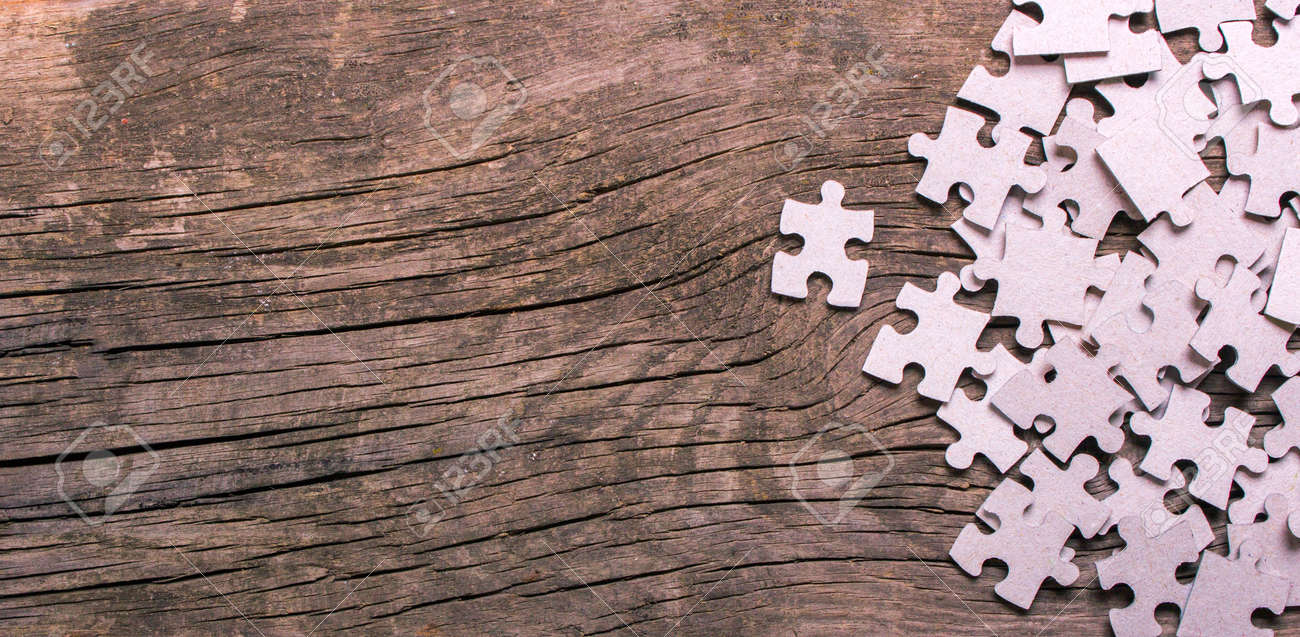 Puzzle pieces with empty space for text on an old wooden table - 75415960