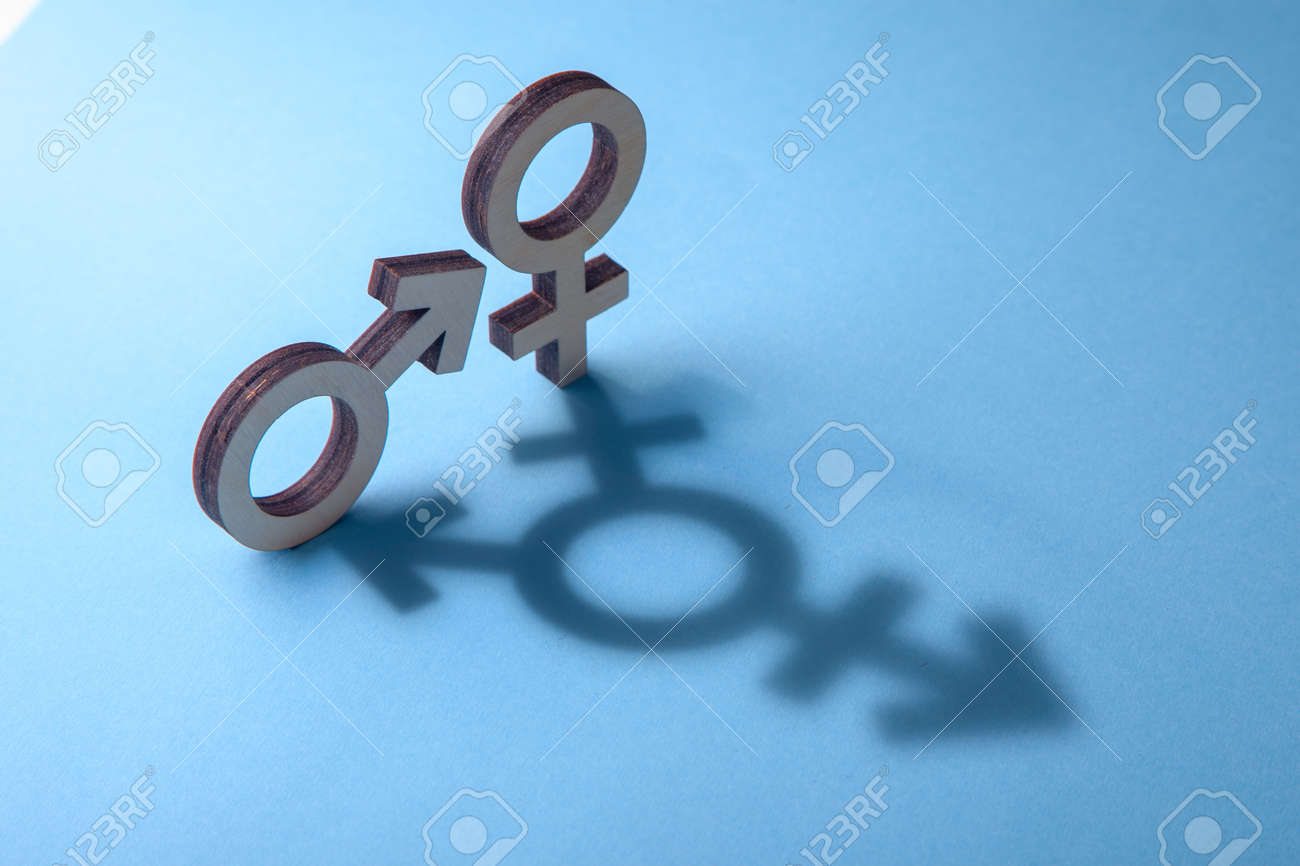 Symbols of man and woman cast shadow in the form of on blue background - 105034961