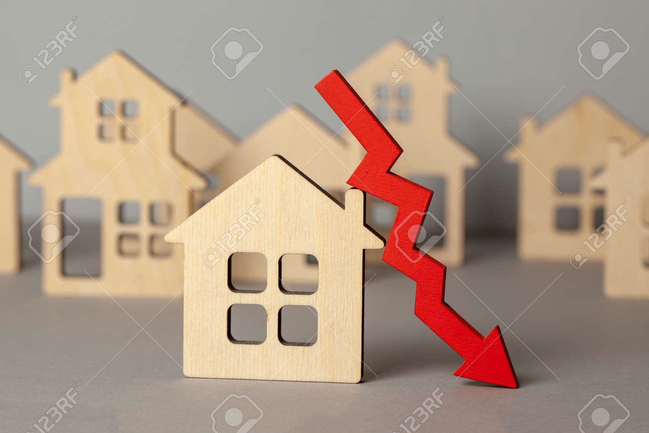 Arrow down and many houses. Falling real estate prices market. Buying and selling house. - 121964904