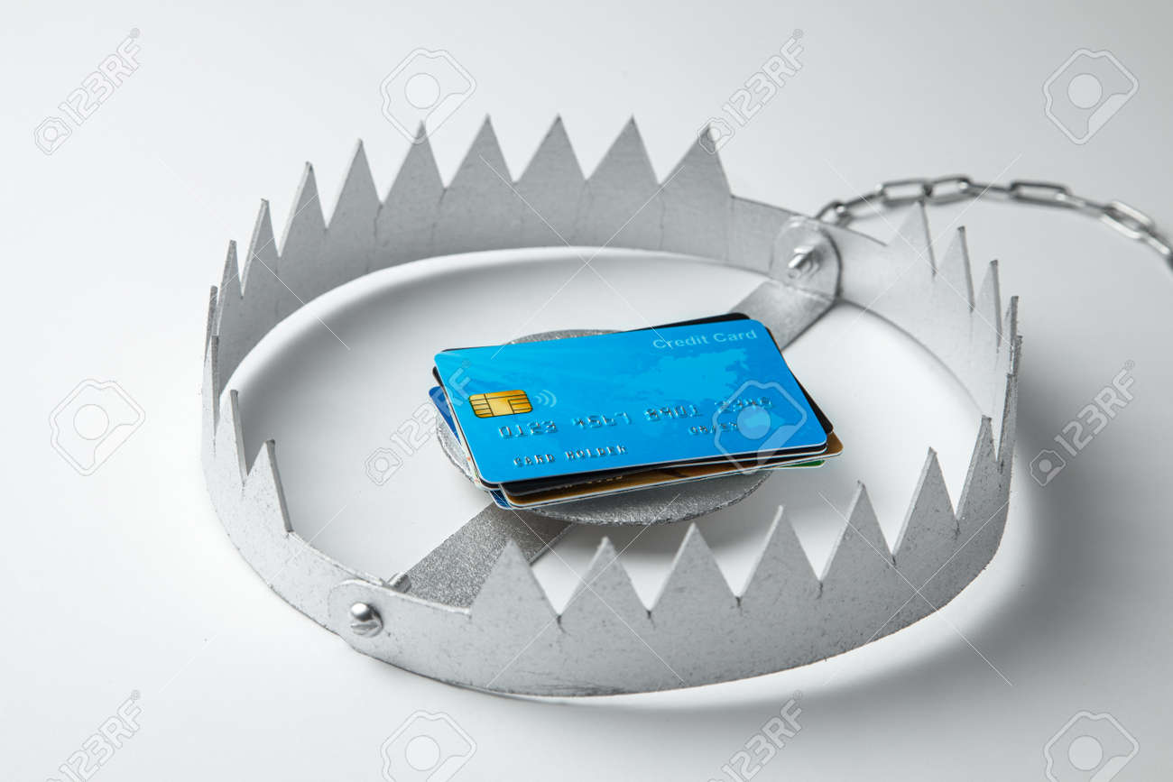 Trap with stack of credit cards. Unsafe credit risk. Gray background - 127411866