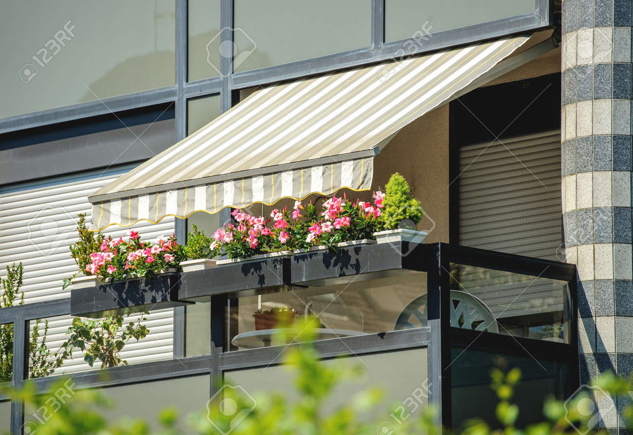Balcony With Awning Opened And Beautiful Flowers