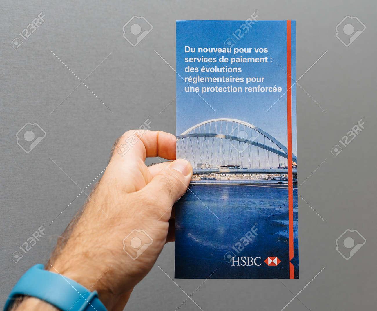 PARIS, FRANCE - NOV 28, 2017: Man hand holding HSBC bank flyer