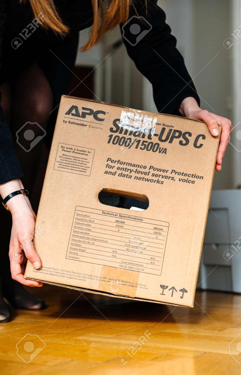 PARIS, FRANCE - MAR 29, 2018: IT woman unboxing APC Smart-UPS