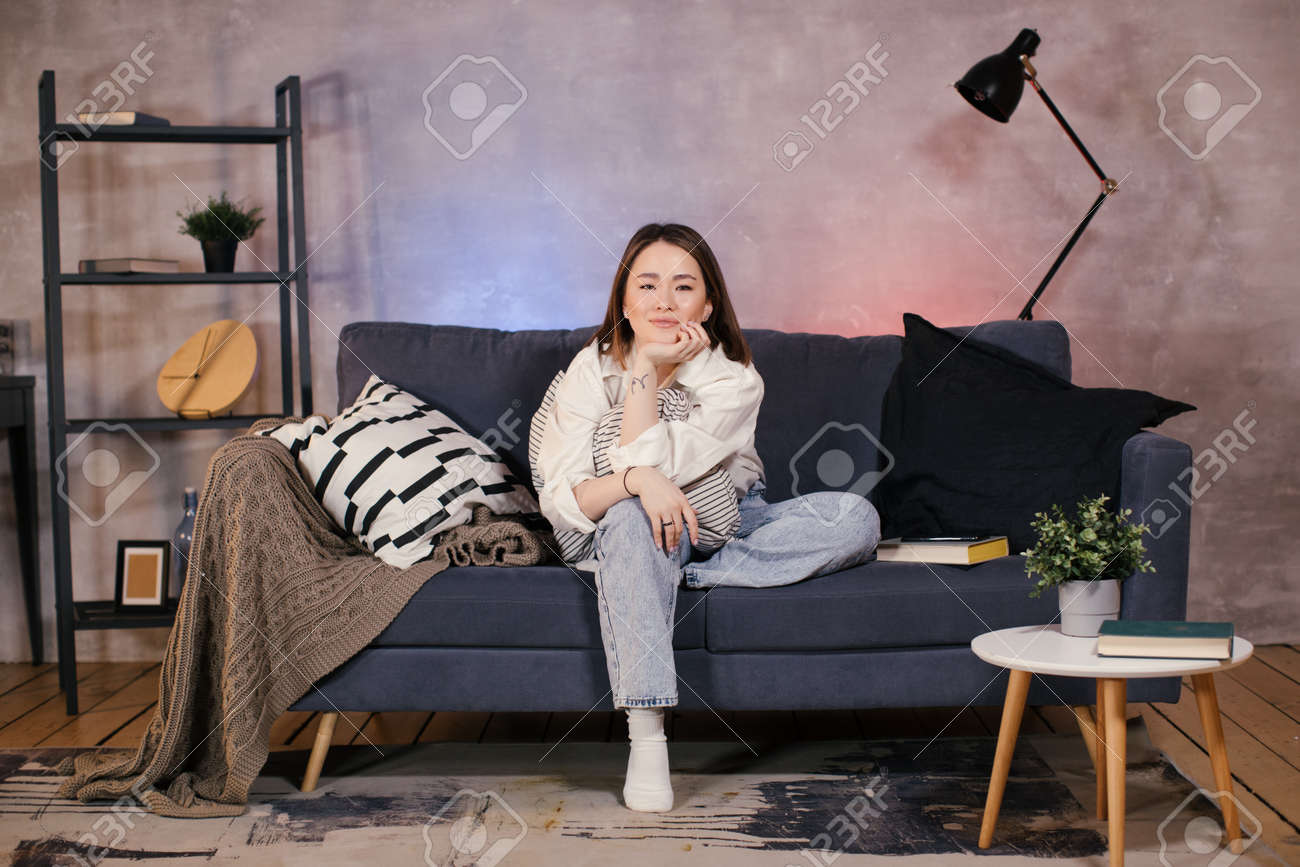 Asian Woman sitting on the couch watching TV and she is funny - 162039487