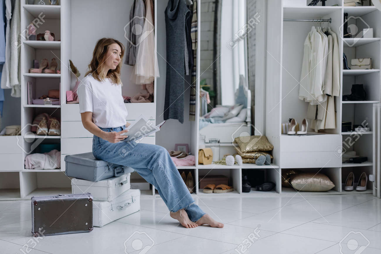 Stylish young female fashion designer dreaming sitting near wardrobe with clothes in cozy modern dressing room - 164447733
