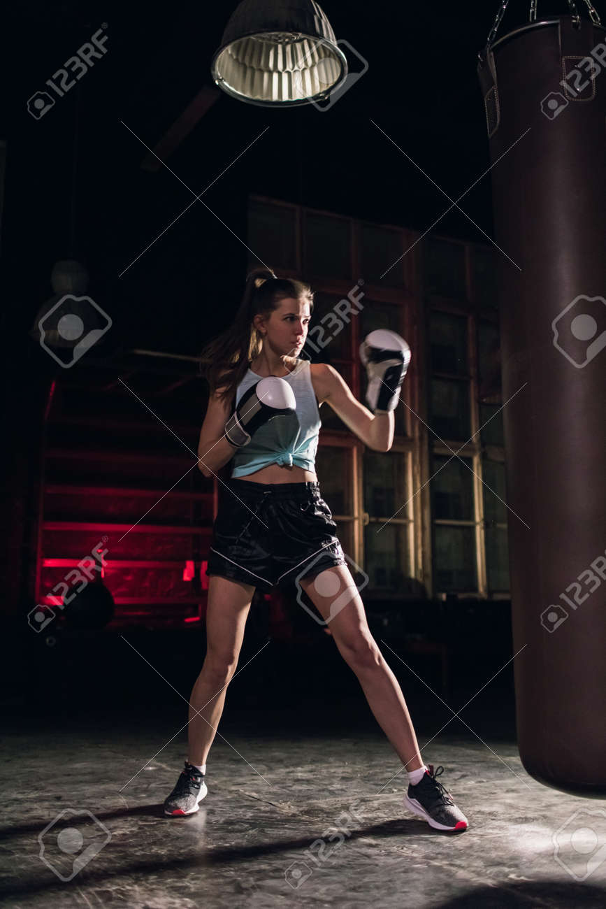 cool female fighter in boxing gloves trains in the gym. Mixed martial arts - 164447736