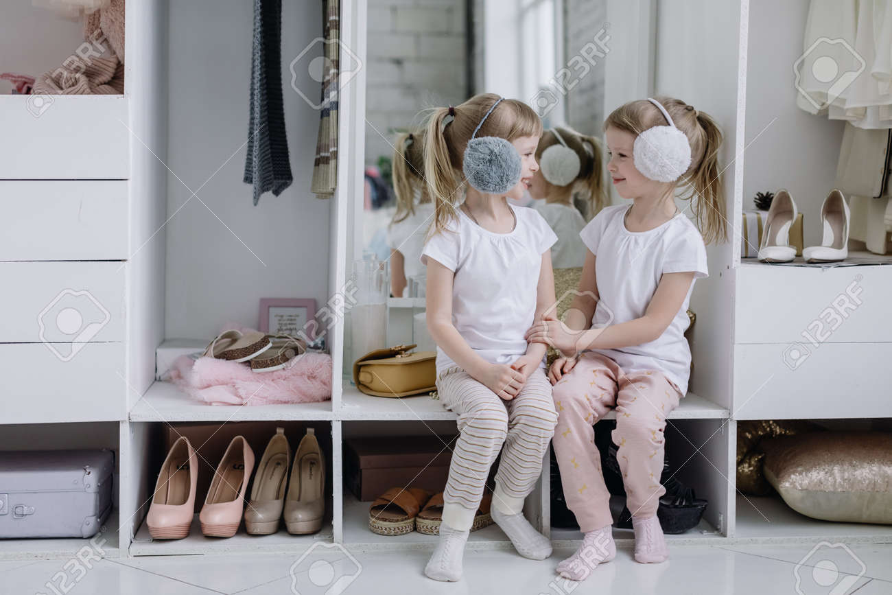 Family wardrobe. Happy twin sisters on shelve in closet with natural organic clothes in cozy dressing room play joyfully - 164447743