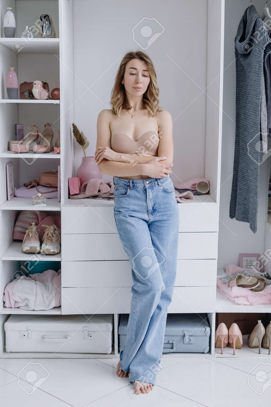 Beautiful young female in beige bodice, jeans posing near closet with clothes in dressing room think what to wear - 164447803