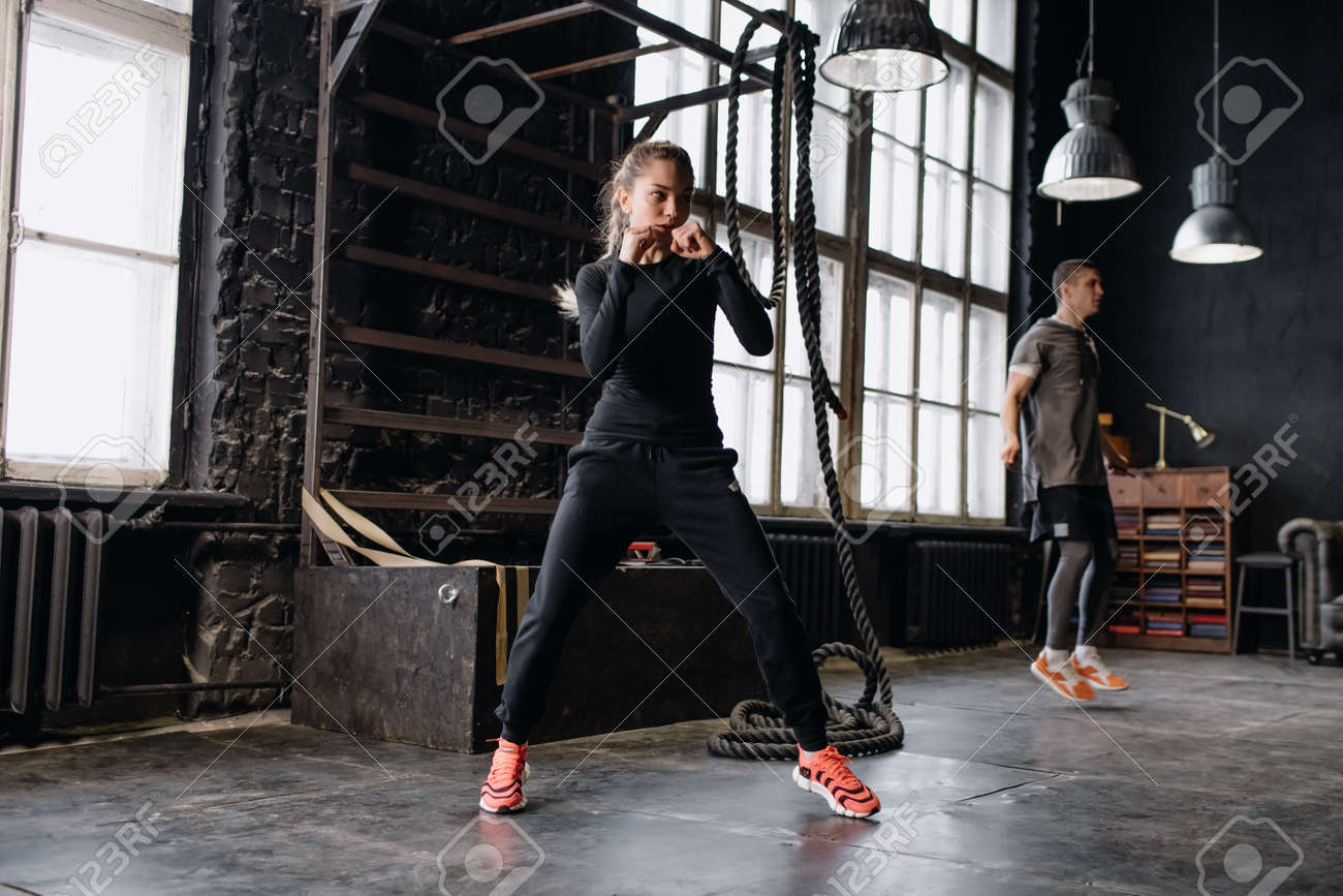 cool female fighter in boxing gloves trains in the gym. Mixed martial arts - 164447807
