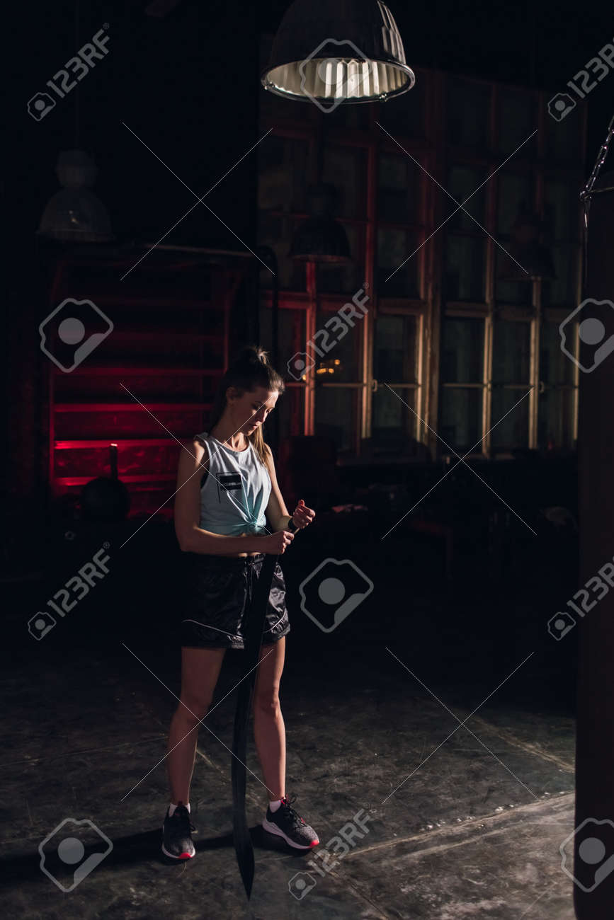 Cool female fighter in boxing bandages trains in gym. Mixed martial arts - 166083817