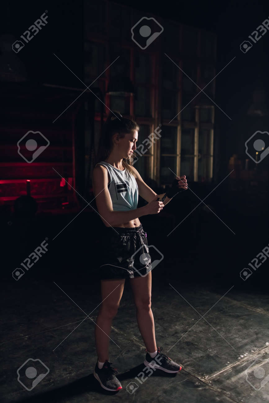 Cool female fighter in boxing bandages trains in gym. Mixed martial arts - 166083820