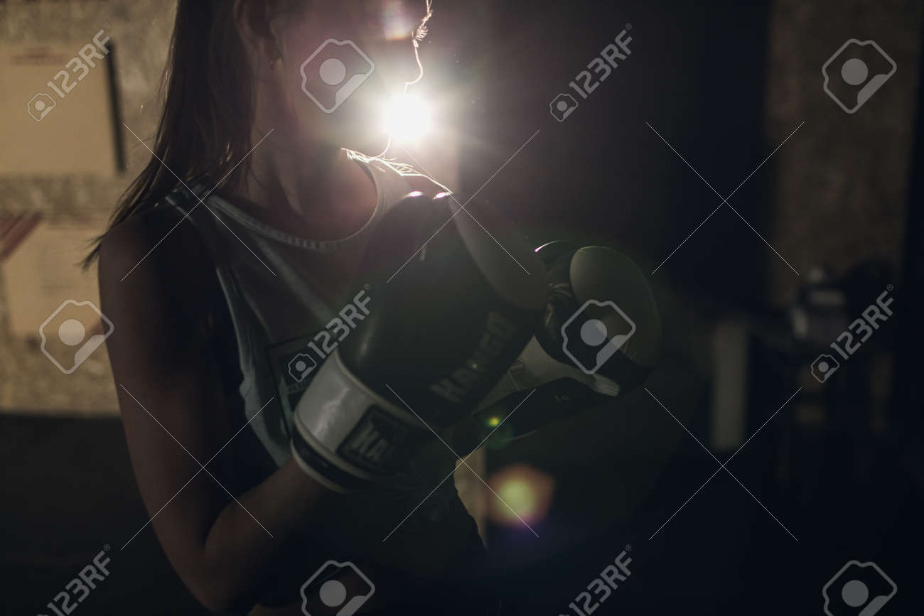 Cool female fighter in boxing bandages trains in gym. Mixed martial arts - 166083823
