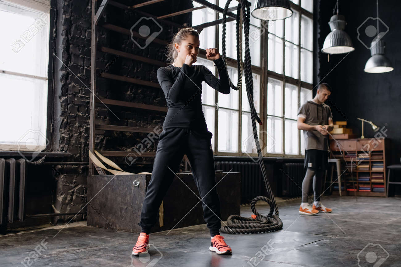 cool female fighter in boxing gloves trains in the gym. Mixed martial arts - 166083832