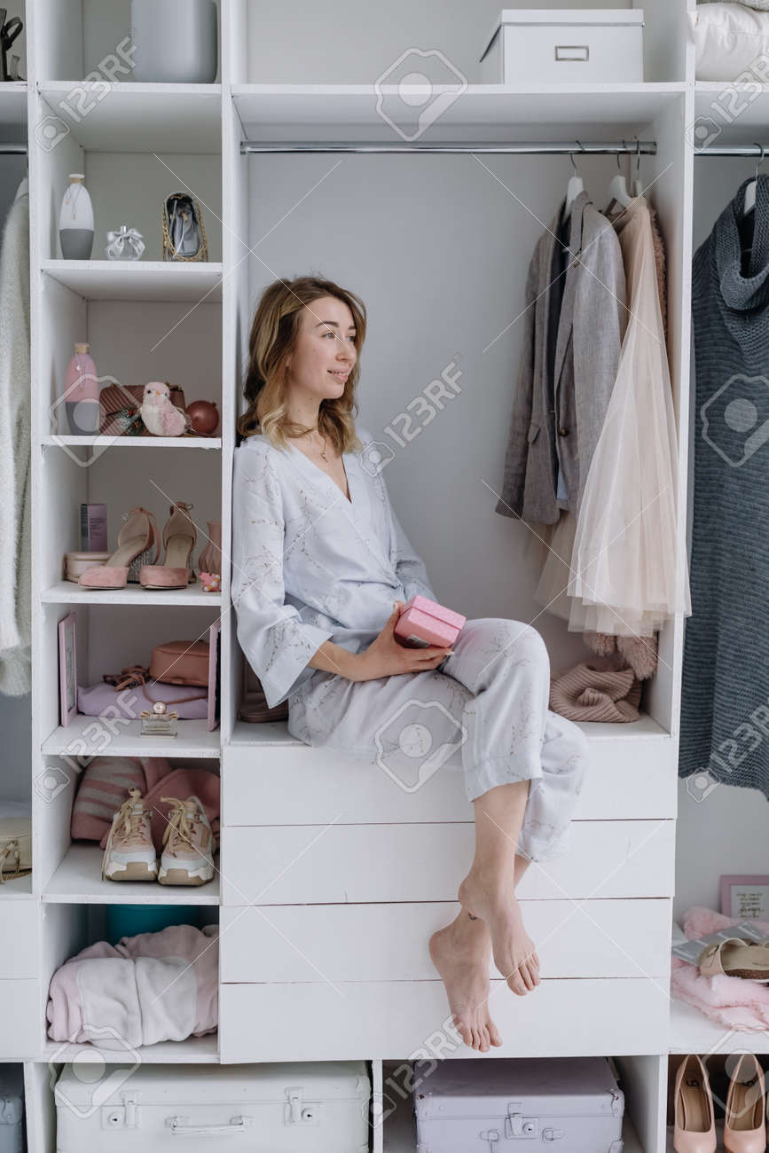 Young woman sits in a modern dressing room with a gift box. Girl dreams of something - 166079675