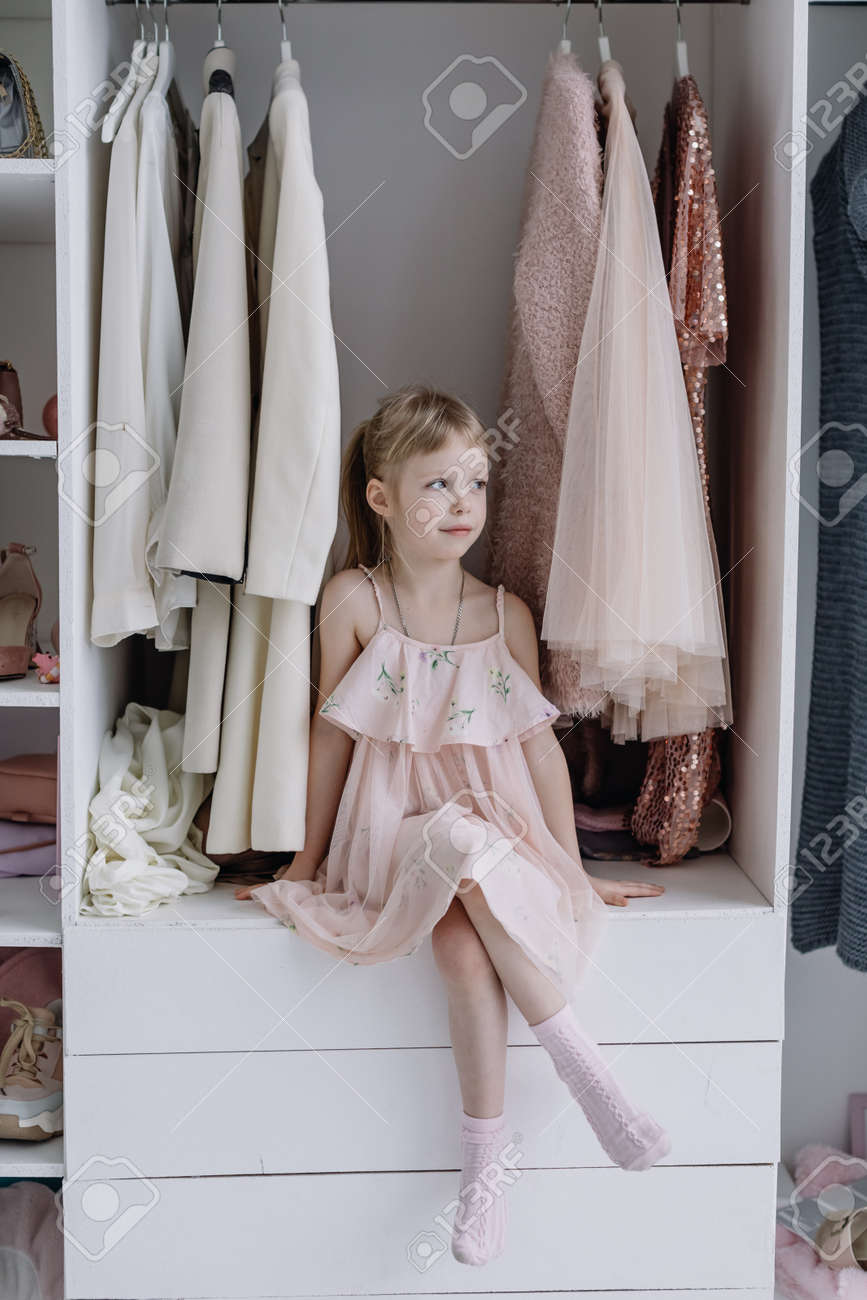 Portrait of A Little Girl in A Beautiful Dress. Girl looks at the camera - 166079631