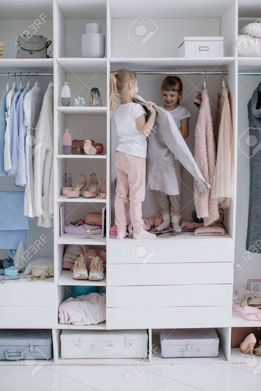 Family wardrobe. Happy twin sisters on shelve in closet with natural organic clothes in cozy dressing room play joyfully - 166079642