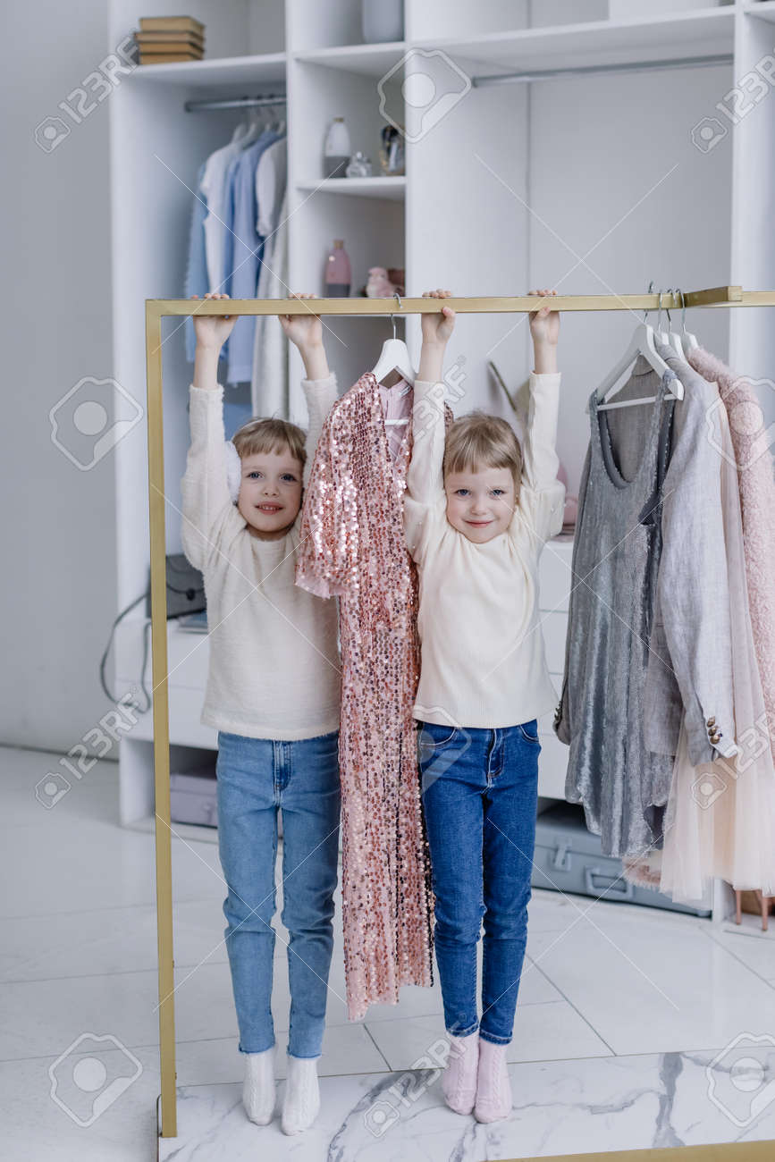 Young mother sits in a modern dressing room with a phone taking selfies with her twin daughters - 166080501